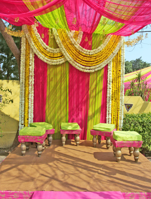 brides house decoration. The mehendi ceremony happened under a beautiful canopy decorated by pink  and green cloth strings of flowers kaleeras hanging off the roof like little indian decor for weddings Unreal Bride